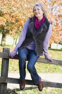 Senior woman sitting on fence with autumn woodland behind