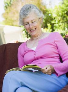 Senior woman sitting on garden seat reading book