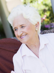 Senior woman sitting outside on garden chair