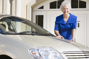 Senior woman standing next to new car outside house