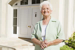 Senior woman standing outside front door of house