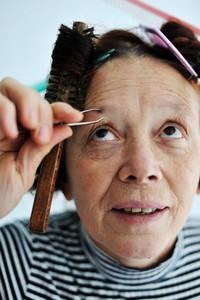 Senior woman tweezing eyebrow
