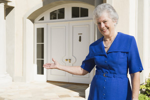 Senior woman welcoming guests to home