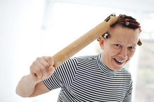 Senior woman with a rolling pin and curlers on hair