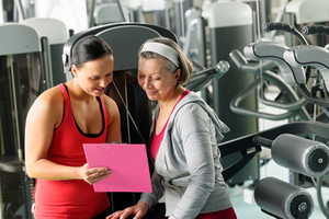 Senior woman with personal trainer looking exercise chart at gym