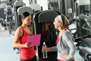 Senior woman with trainer discuss personal plan at gym