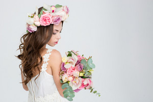 Sensual attractive young woman with long curly beautiful hair in roses wreath holding bouquet of flowers over white background