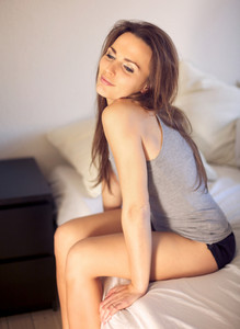Sensual woman sitting on top of her bed smiling alone