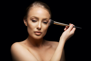 Sensual young woman applying make up with a brush against black background. Pretty young caucasian model.