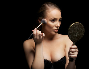 Sensual young woman wearing bra applying foundation on her face with a make up brush. Caucasian female fashion model holding mirror applying make up against black background.