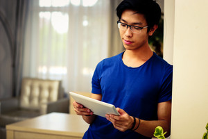 Serious asian man using tablet computer at home