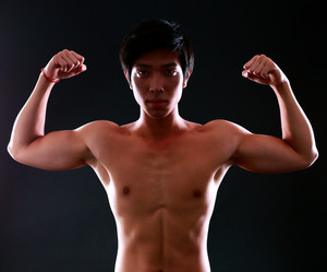 Serious asian muscular man with his arms stretched out on black background