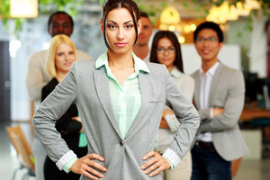 Serious beautiful businesswoman standing in front her colleagues