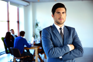 Serious businessman standing with arms folded in front of colleagues