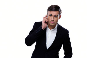 Serious businessman talking on the phone over white background