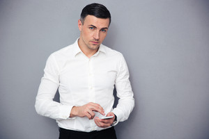 Serious businessman using smartphone