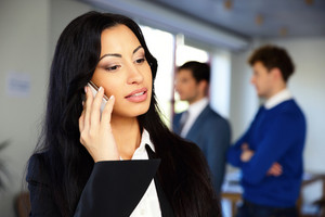 Serious businesswoman talking on the phone with colleagues on background