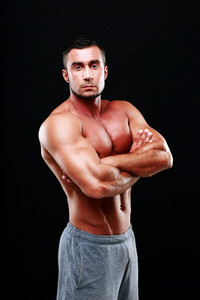 Serious muscular man with arms folded standing over white background