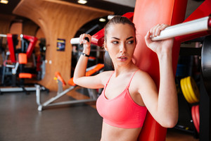 Serious pretty young woman athlete in pink top working out in gym