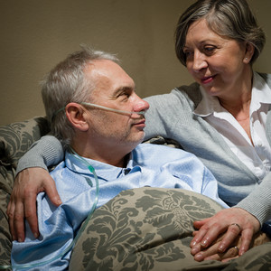 Seriously ill old man lying in bed with loving wife