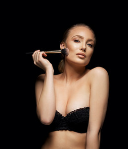 Sexy female model applying holding a makeup brush with an attitude. Upper body portrait.