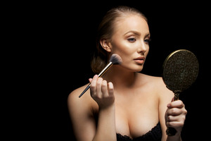 Sexy woman applying foundation on her face with a make up brush. Caucasian female fashion model holding mirror applying make up against black background.