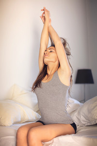 Sexy woman sitting on top of her bed doing early morning stretching