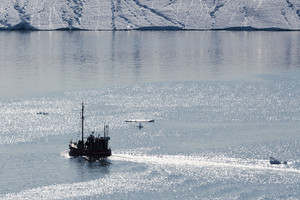 Ship traveling in sunlit waters past an iceberg