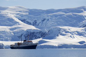Ship traveling past a sunlit, snowy coast