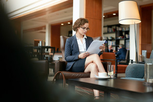 Shot of young business executive sitting at coffee shop reading documents. Caucasian business woman going through some papers.