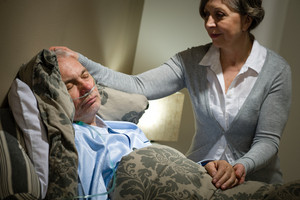 Sick lying senior man with caring wife at home