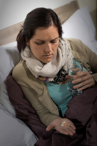 Sick woman holding and looking at medicine pills flu cold