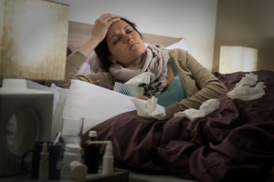 Sick woman in bed suffering from flu headache