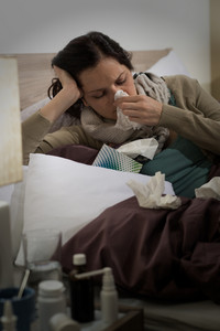 Sick woman with flu sneezing blowing her nose in bed