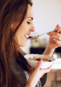 Side view of a  healthy woman smiling while eating her cereals