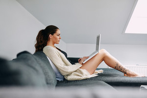 Side view of attractive young lady sitting on sofa using laptop. Caucasian female model on couch surfing internet on laptop computer at home.