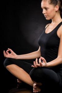 Side view of relaxed young woman exercising in lotus position