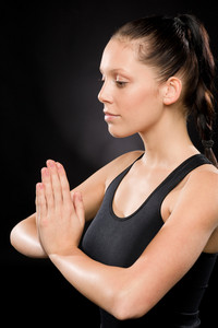 Side view of tranquil woman performing yoga with eyes closed
