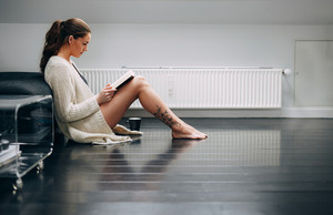 Side view of young woman relaxing on floor reading book. Pretty young lady sitting on floor at home reading a novel.