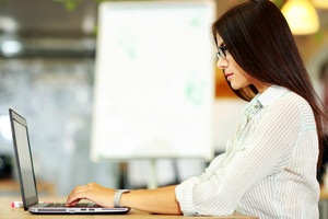Side view portrait of a businesswoman working on the laptop at office