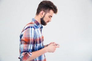 Side view portrait of a happy man using smartphone