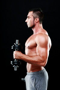 Side view portrait of a sportsman lifting dumbbells over black background