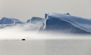 Silhouette of a boat traveling by an iceberg on a foggy day
