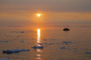Silhouette of a boat traveling icy waters at sunset