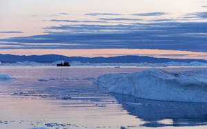 Silhouette of a boat traveling through an ice field at dusk