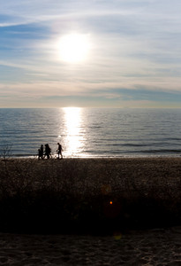 Silhouette of a family walking along the New England shoreline with lens flare.