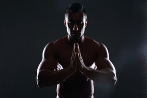 Silhouette of a muscular man praying