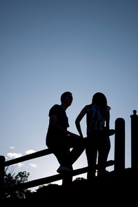 Silhouette of a young couple hanging out together outdoors by an old country fence during the early evening hours.