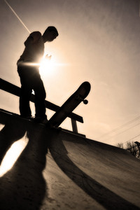 Silhouette of a young skateboarder at the top of the ramp.