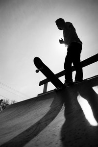 Silhouette of a young teenage skateboarder at the top of the half pipe ramp at the skate park.